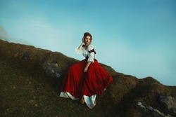 Beautiful red-haired girl is sitting on the stones covered with moss, over the precipice at the background of mountains and mist.