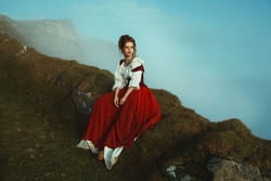 Beautiful red-haired girl is sitting on the stones covered with moss, over the precipice at the background of mountains and mist