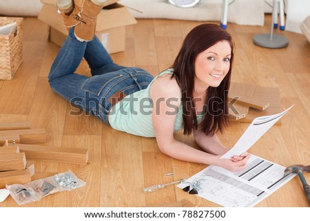 Beautiful red-haired girl posing while reading a manual before do-it-yourself at home