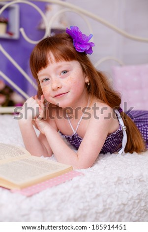 beautiful red-haired girl reading a book room