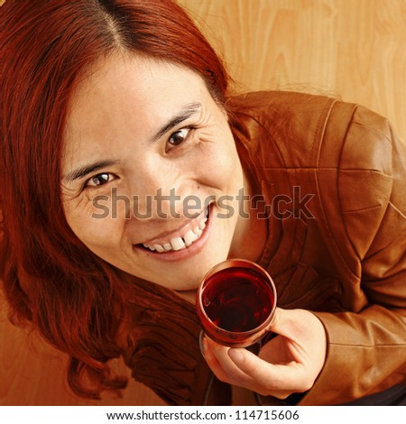 Beautiful Red Haired Girl with a Glass of Red Wine