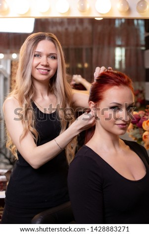 Beautiful, red-haired girl with long hair, hairdresser weaves a French braid, in a beauty salon. Professional hair care and creating hairstyles. #1428883271