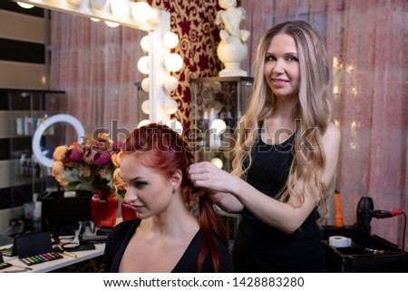 Beautiful, red-haired girl with long hair, hairdresser weaves a French braid, in a beauty salon. Professional hair care and creating hairstyles. #1428883280