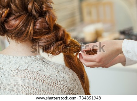 Beautiful, red-haired girl with long hair, hairdresser weaves a French braid, in a beauty salon. Professional hair care and creating hairstyles. #734851948