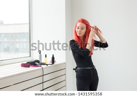 Beautiful red-haired girl with long hair, she is weaves a braid, in a beauty salon. Professional hair care and creating hairstyles. #1431595358