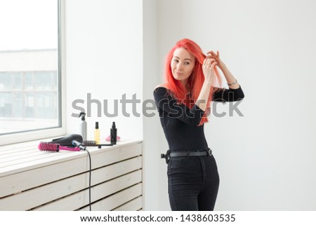 Beautiful red-haired girl with long hair, she is weaves a braid, in a beauty salon. Professional hair care and creating hairstyles.