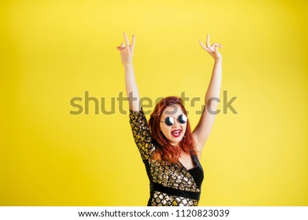 beautiful red-haired woman in sunglasses dancing dance in yellow background in studio #1120823039