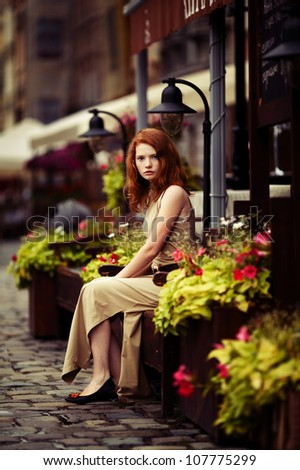 beautiful red-haired woman resting on the streets of the beautiful city