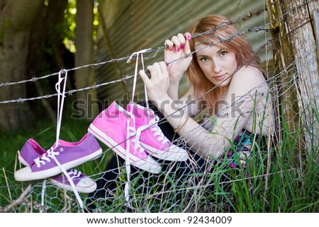 Beautiful Red Haired Woman wearing casual clothes in a rural setting with farm fence and sneakers hanging on fence