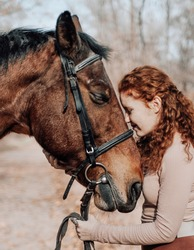 Beautiful red haired woman with horse posing outdoors on autumn background