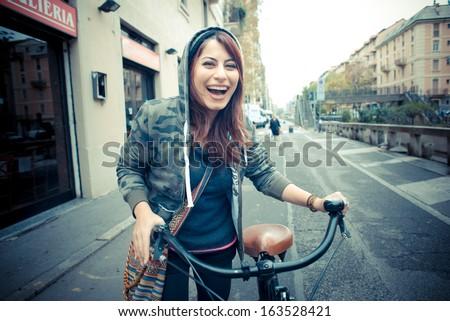 beautiful red head womanon bike in the city
