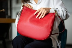 Beautiful red leather purse in the girl's hand. Luxury bag on the background of black trousers in the interior. Fashionable modern accessory. horizontal photo