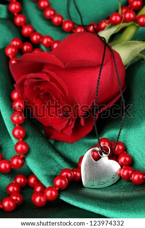 Beautiful red rose with heart pendant - stock photo