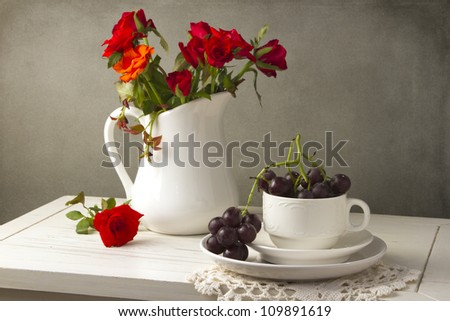 Beautiful red roses and grapes with white tableware