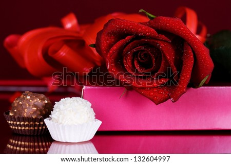 beautiful red roses with chocolates on a red background