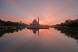 Beautiful red sky during sunrise with lake reflection at Putrajaya Lake Garden.  Motion Blur, Soft Focus due to Slow Shutter Speed. Copy Space Area.