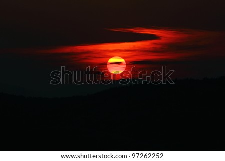 Beautiful red sunset over the forests. Sun through the clouds  reaching the horizon at dusk.