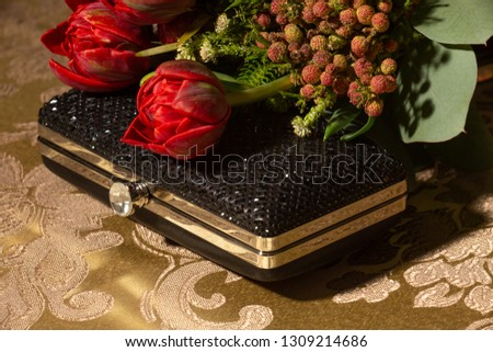 Beautiful Red tulip bouquet of fowers and black clutch on formal table for formal event, wedding, or prom. #1309214686