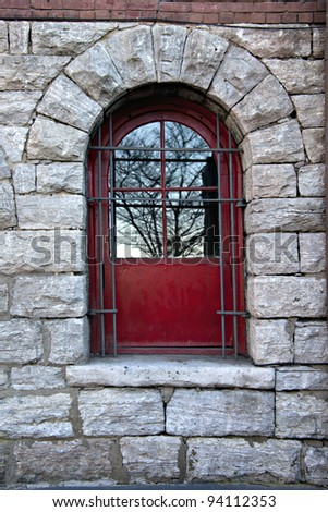 Beautiful red window or door in old stone wall with steel security bars and reflections of trees