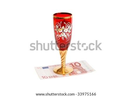 Beautiful red wine glass  with golden stem on ten euro bill isolated