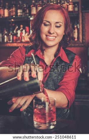 Beautiful redhead barmaid making cocktail