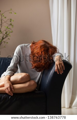 beautiful redhead depressed on a couch