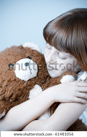 Beautiful redhead girl hugs a teddy bear.