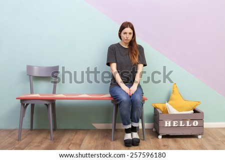 Beautiful redhead girl left alone on a two seats bench. Looking sad at the camera. Hello box.
