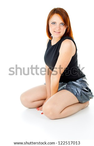 beautiful redhead girl sitting isolated on white background