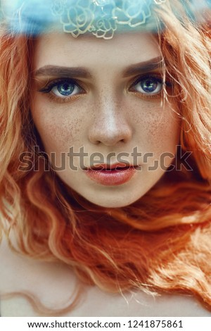Beautiful redhead Norwegian girl with big eyes and freckles on face in the forest. Portrait of redhead woman closeup in nature, fabulous mysterious appearance long wavy red hair in the sun. Hair care
