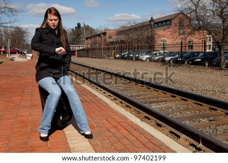Beautiful redhead sitting on her luggage waiting for the train