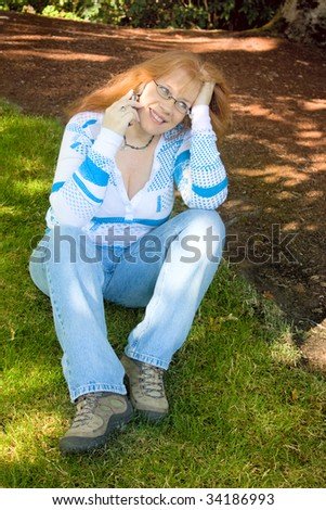 Beautiful Redhead Woman day dreaming and talking on Cell Phone sitting on green grass under the shadows of a tree. She\'s wearing blue jeans and is wearing glasses and a necklace.