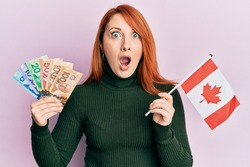 Beautiful redhead woman holding canadian dollars and canada flag afraid and shocked with surprise and amazed expression, fear and excited face.
