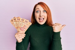 Beautiful redhead woman holding 100 mexican pesos banknotes pointing thumb up to the side smiling happy with open mouth