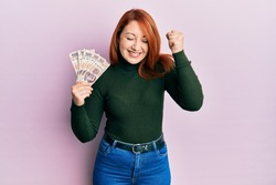 Beautiful redhead woman holding 500 mexican pesos banknotes screaming proud, celebrating victory and success very excited with raised arm