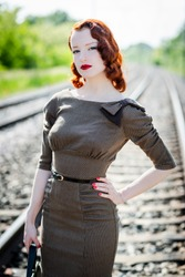 beautiful redhead woman in vintage clothes on railway