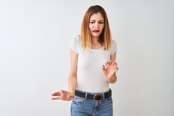Beautiful redhead woman wearing casual t-shirt standing over isolated white background disgusted expression, displeased and fearful doing disgust face because aversion reaction. With hands raised.