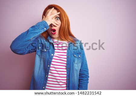 Beautiful redhead woman wearing denim shirt and striped t-shirt over isolated pink background peeking in shock covering face and eyes with hand, looking through fingers with embarrassed expression.