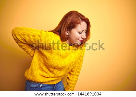 Beautiful redhead woman wearing winter sweater standing over isolated yellow background Suffering of backache, touching back with hand, muscular pain