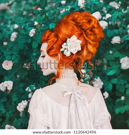 Beautiful redhead woman with high hairdo in a white dress on rose background. Portrait of young unusual pale girl with red hair. Beautiful model with stylish hairdo with a rose in garden