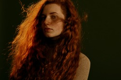 Beautiful redhead woman with natural long curly hair posing on dark olive green background. Hair care, beauty conception. Copy, empty space for text