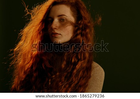 Beautiful redhead woman with natural long curly hair posing on dark olive green background. Hair care, beauty conception. Copy, empty space for text Сток-фото ©