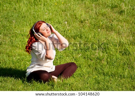 beautiful redhead young woman listening to music with headphones on nature, outdoors, on grass lawn