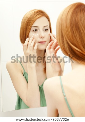 Beautiful redhead young woman with cream on the face in bathroom - stock photo