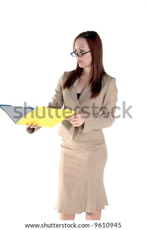 Beautiful Redheaded Executive reviewing a file in the office - stock photo