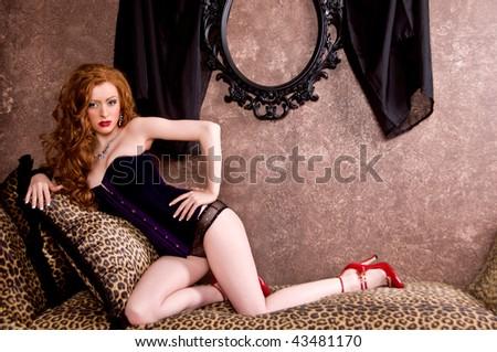 Beautiful redheaded model in purple velvet corset