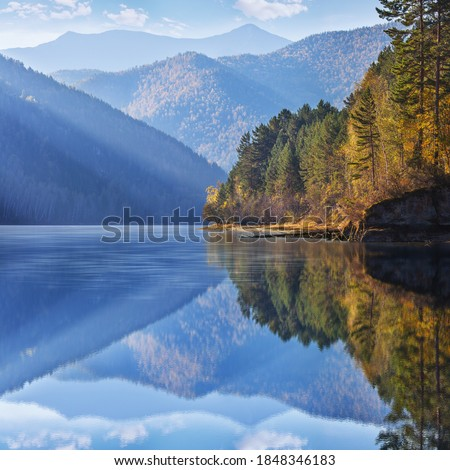 Photo of  Beautiful reflection in clear water. The calm flow of the Yenisei River in Siberia. Autumn view.