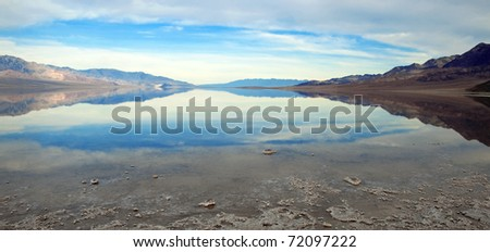 Beautiful reflection of blue sky on flooded Badwater Basin, Death Valley National Park, California.