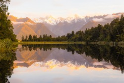 Beautiful reflection of mountain and trees in lake Matheson, South Newzealand.