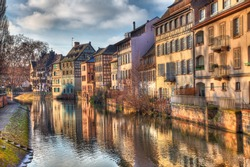 Beautiful reflections at the sunset of traditional buildings in a water canal in Strasbourg in eastern France.